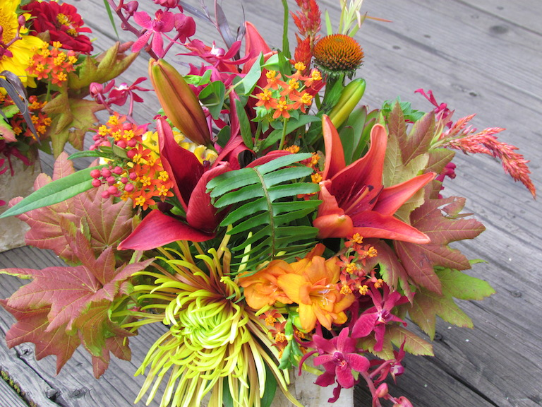 Spider mums, ferns and autumn leaves accent this bridal bouquet
