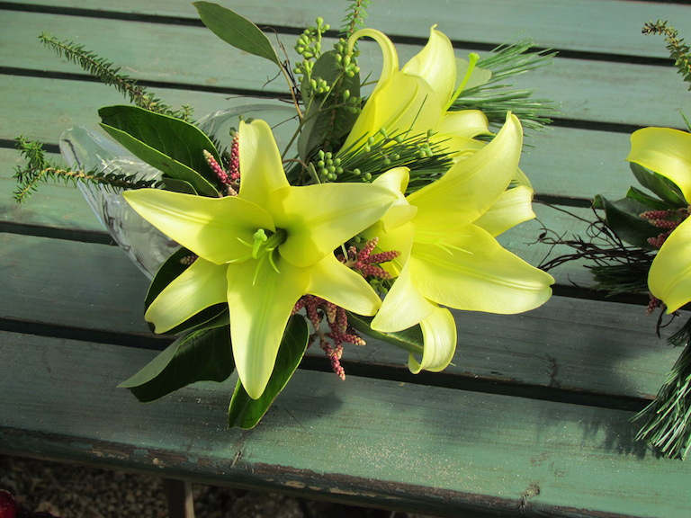 Yellow lilies in a clear glass flute.