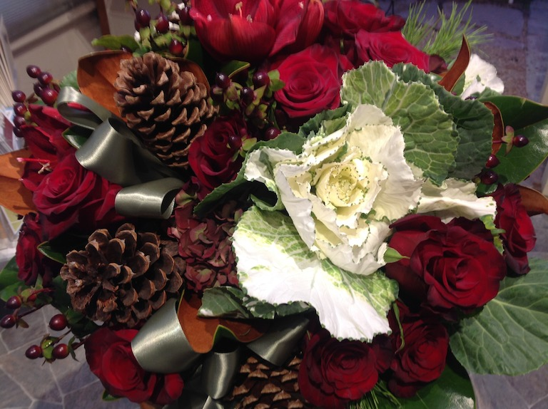 Red roses, red amaryllis and flowering kale with silk ribbon