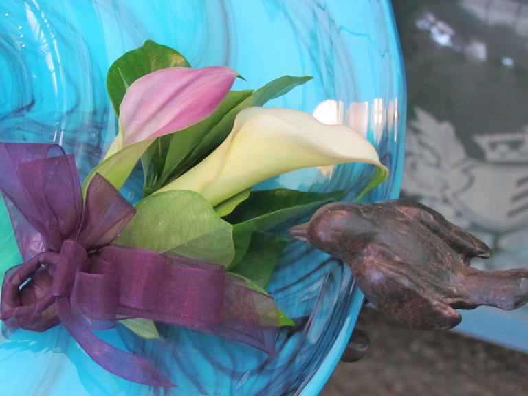 Miniature calla lilies in a corsage with purple ribbon