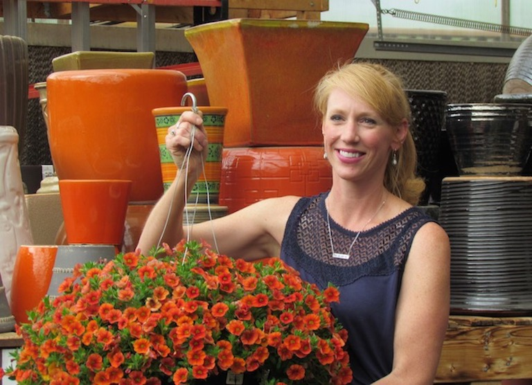 Mandy with orange pots that match her favorite hanging basket