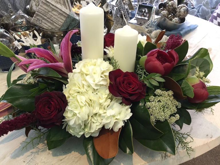 Christmas arrangement with magnolia leaves, roses and candles