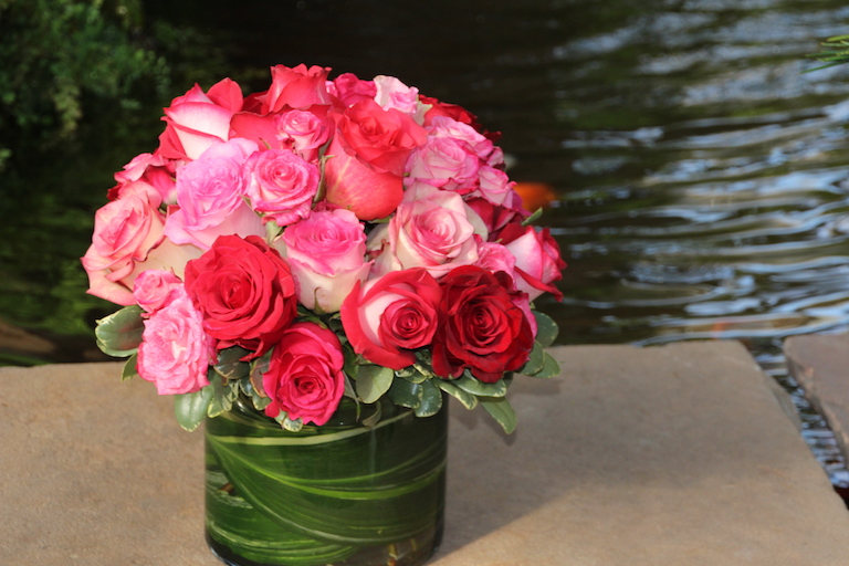 Mixed red and pink roses in a glass cylinder lined with greens